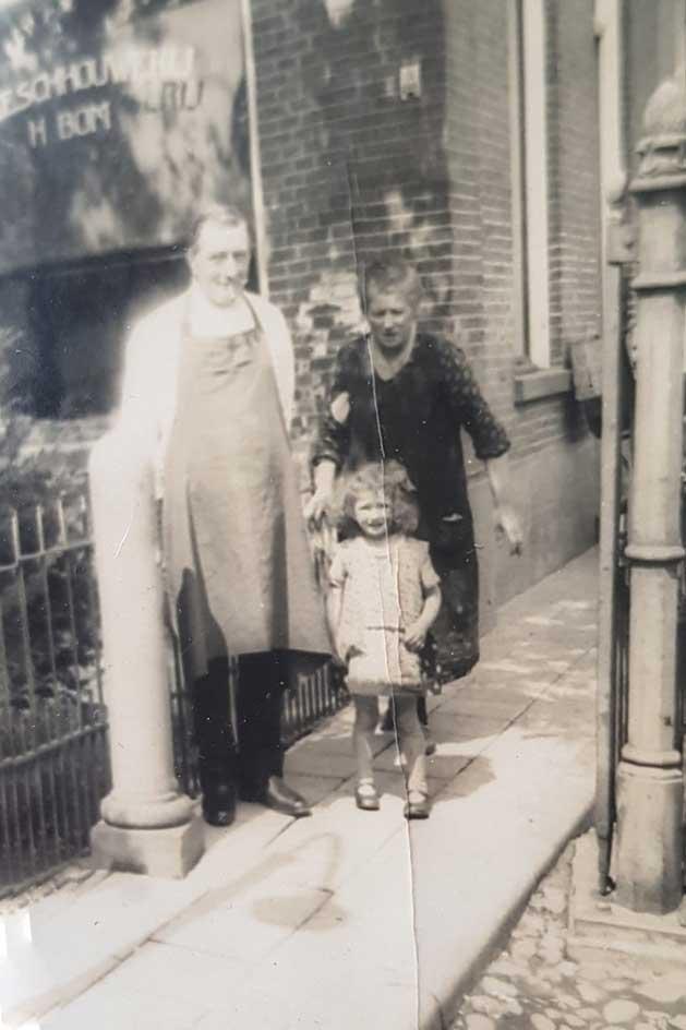 Fredrik Hendrik Bom voor de slagerij met schoondochter Dina en kleindochter Lena Bom